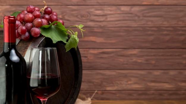 Botte di legno con bottiglia e bicchiere di vino Foto Gratuite