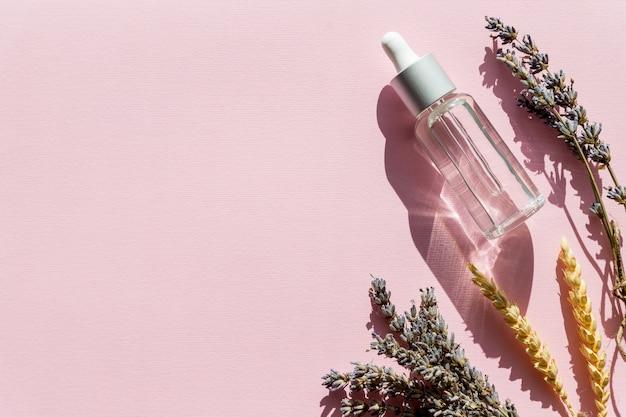 Bottiglia con olio aromatico e fiori di lavanda. prodotto per la cura del corpo all'olio di lavanda. aromaterapia, spa, assistenza sanitaria naturale. copi lo spazio Foto Premium