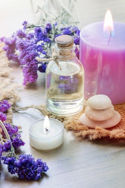 Bottiglia con olio essenziale di lavanda, candela sul tavolo di legno. Foto Premium