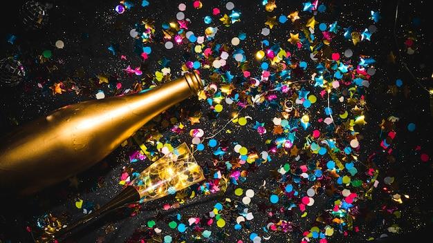 Bottiglia con vetro sul tavolo nero Foto Gratuite