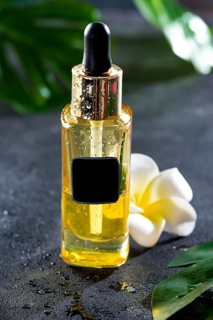 Bottiglia contagocce con fiori e foglie verdi su una pietra scura Foto Premium