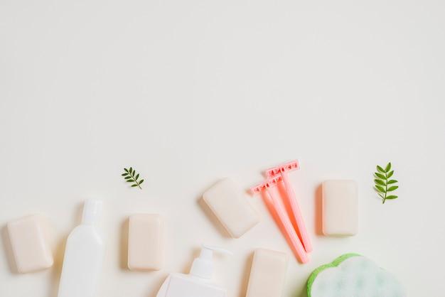 Bottiglia dell'erogatore; sapone e rasoio rosa su sfondo bianco Foto Gratuite