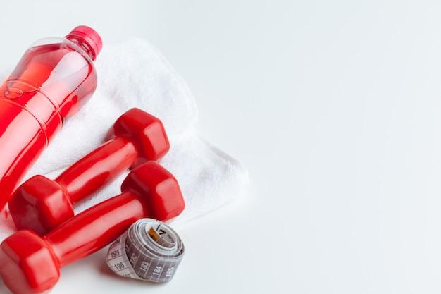 Bottiglia di acqua ed attrezzatura di forma fisica isolate su bianco Foto Premium