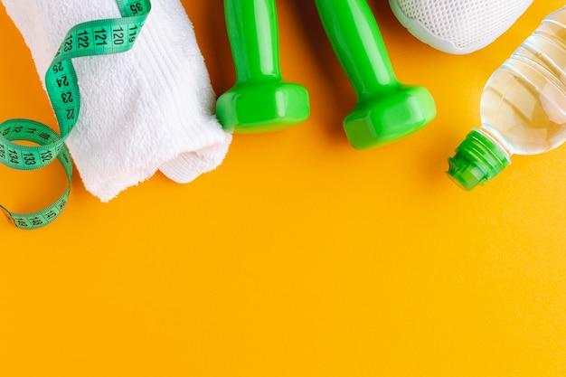 Bottiglia di asciugamano e pesi con copia spazio Foto Gratuite