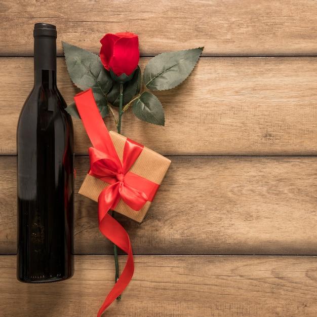 Bottiglia di bevanda vicino presente e fiore Foto Gratuite