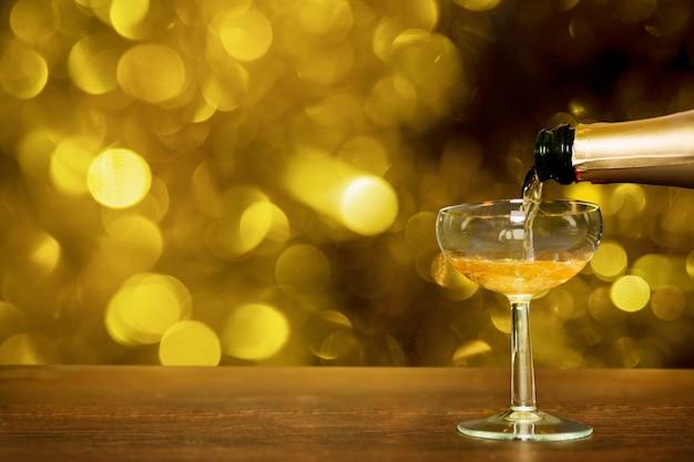 Bottiglia di champagne che versa in vetro con effetto bokeh Foto Gratuite