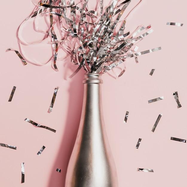 Bottiglia di champagne con coriandoli alla festa di capodanno Foto Gratuite