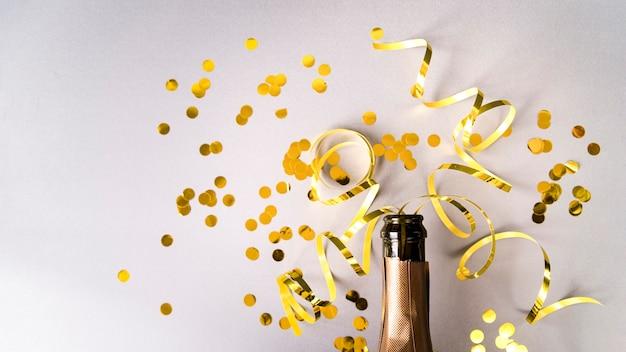 Bottiglia di champagne con coriandoli dorati e stelle filanti su sfondo bianco Foto Gratuite
