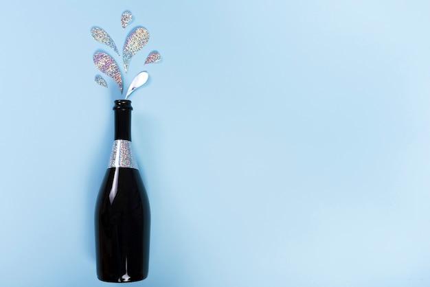 Bottiglia di champagne con schizzi di glitter di ritaglio Foto Gratuite