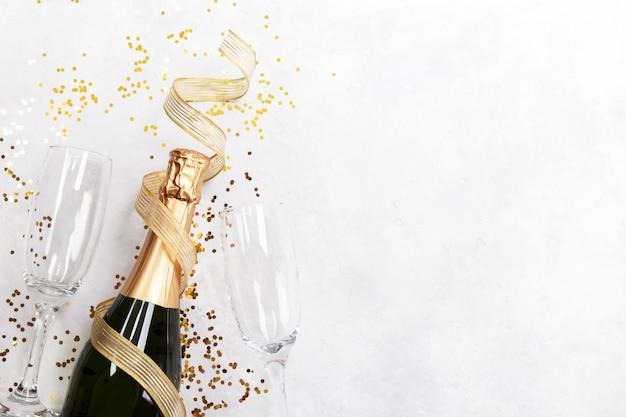 Bottiglia di champagne due bicchieri e coriandoli Foto Premium
