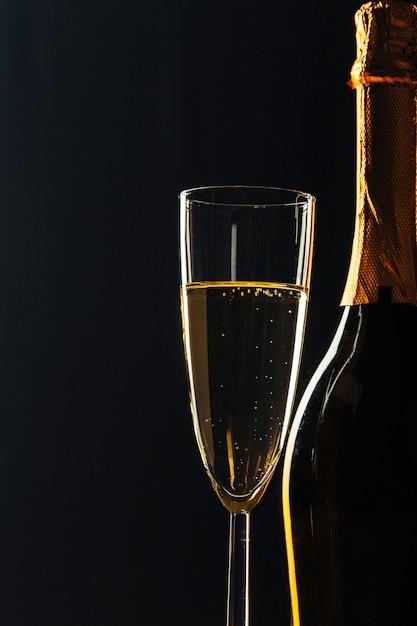 Bottiglia di champagne e bicchieri nel buio Foto Premium