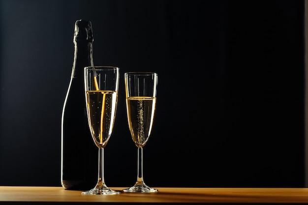 Bottiglia di champagne e bicchieri su sfondo scuro Foto Premium
