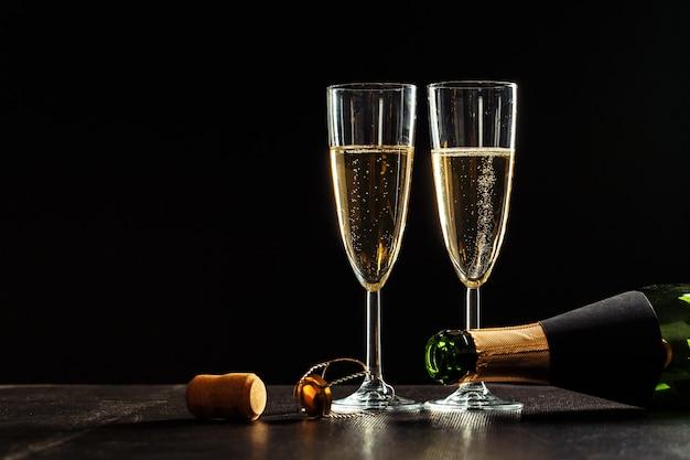 Bottiglia di champagne e bicchieri sul buio Foto Premium