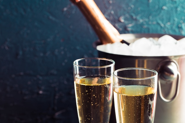 Bottiglia di champagne nel secchio con ghiaccio e bicchieri di champagne Foto Premium