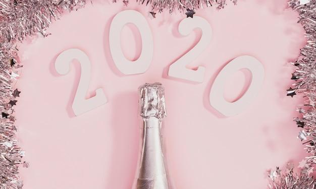 Bottiglia di champagne non aperto con cornice in tinsel Foto Gratuite