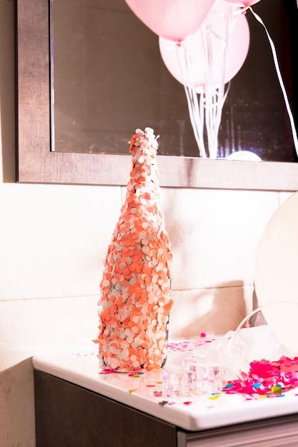 Bottiglia di champagne ricoperta di coriandoli arancioni e bianchi sulla scrivania Foto Gratuite