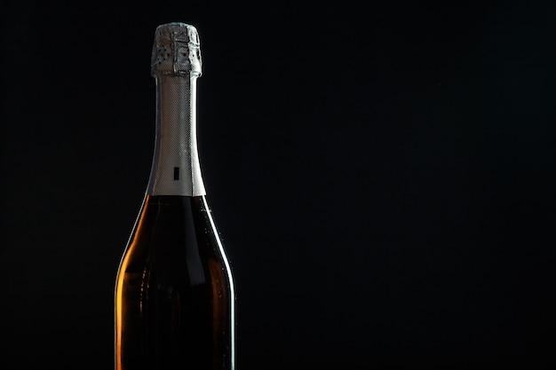Bottiglia di champagne sul nero Foto Premium