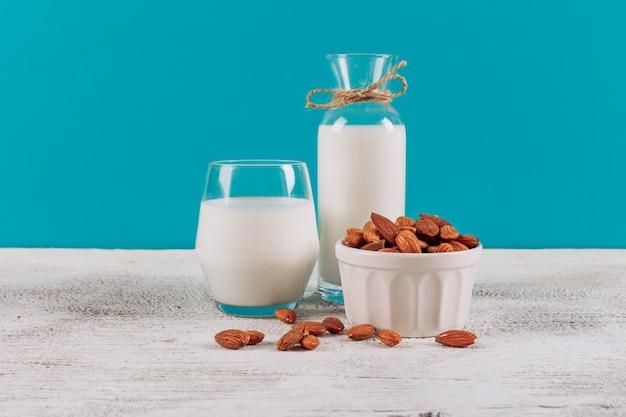 Bottiglia di latte con bicchiere di latte e ciotola di mandorle vista laterale su uno sfondo bianco in legno e blu Foto Gratuite