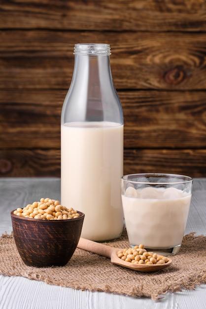 Bottiglia di latte di soia con semi di soia sul tavolo bianco su sfondo di legno scuro Foto Premium