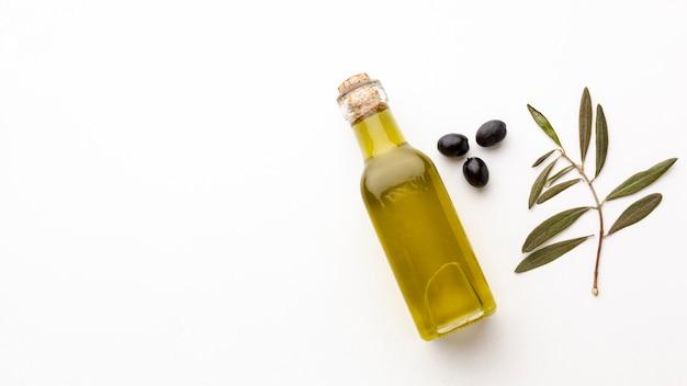 Bottiglia di olio d'oliva con foglie e olive nere con spazio di copia Foto Gratuite