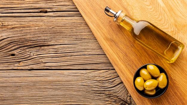 Bottiglia di olio d'oliva e olive gialle con spazio di copia Foto Gratuite