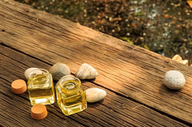 Bottiglia di olio essenziale aroma o spa con pietra zen sulla tavola di legno Foto Premium