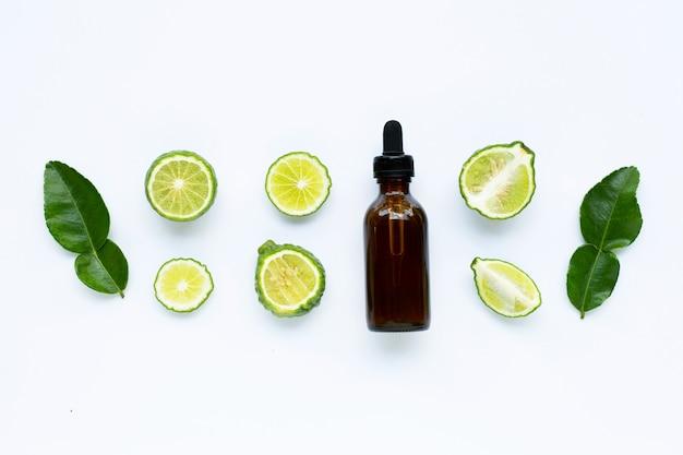 Bottiglia di olio essenziale con lime fresco di kaffir o frutta di bergamotto Foto Premium