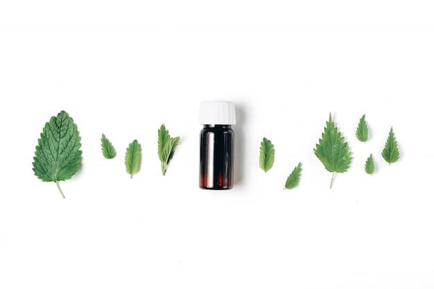 Bottiglia di olio essenziale con ortica fresca e menta piperita su bianco Foto Premium