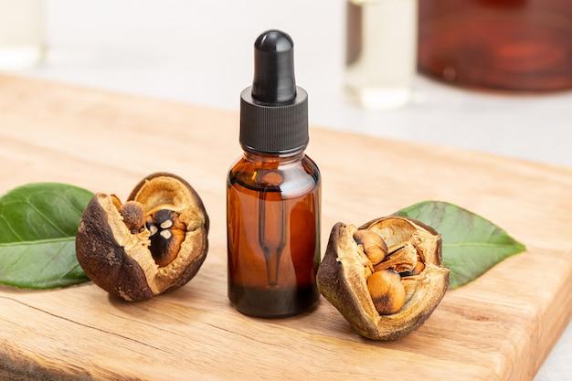 Bottiglia di olio essenziale di camelia e semi di camelia sul tavolo di legno. bellezza, cura della pelle, benessere Foto Premium