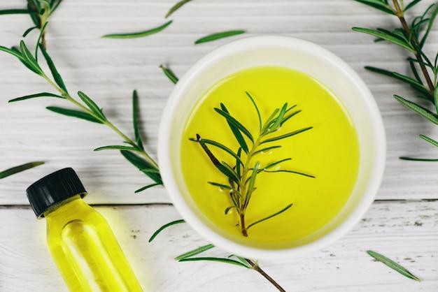 Bottiglia di olio essenziale ingredienti spa naturali olio di rosmarino per aromaterapia e foglie di rosmarino su fondo di legno - cosmetici biologici con estratti di erbe Foto Premium