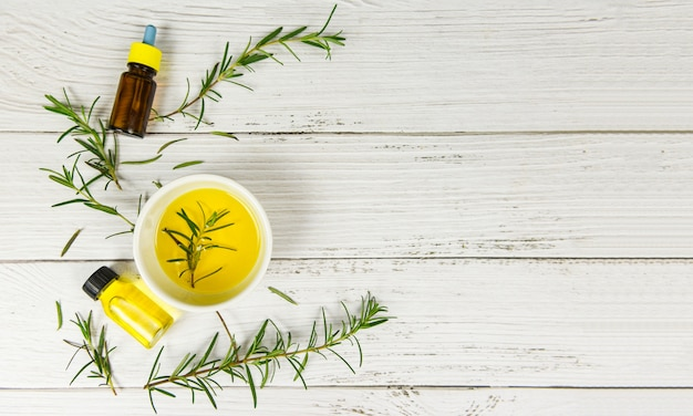 Bottiglia di olio essenziale ingredienti spa naturali olio di rosmarino per aromaterapia e foglie di rosmarino su fondo in legno / cosmetici biologici con estratti di erbe Foto Premium