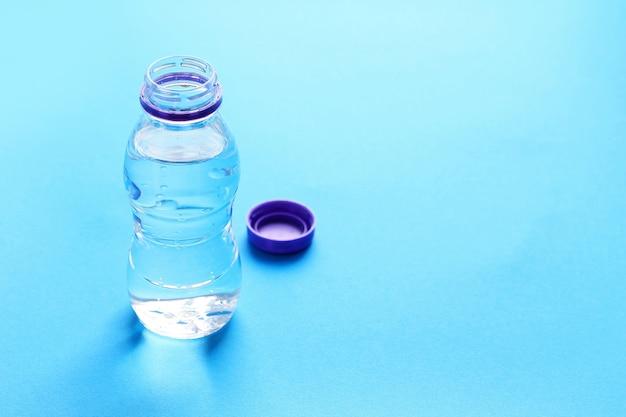 Bottiglia di plastica con acqua sul blu. Foto Premium