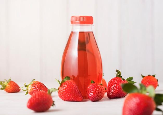Bottiglia di plastica della bevanda del succo di soda delle bacche su fondo di legno con le fragole fresche Foto Premium