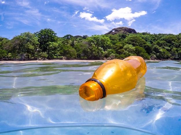 Bottiglia di plastica nell'oceano, riciclaggio Foto Premium