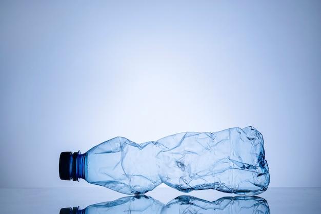 Bottiglia di plastica trasparente vuota sgualcita sull'azzurro Foto Premium