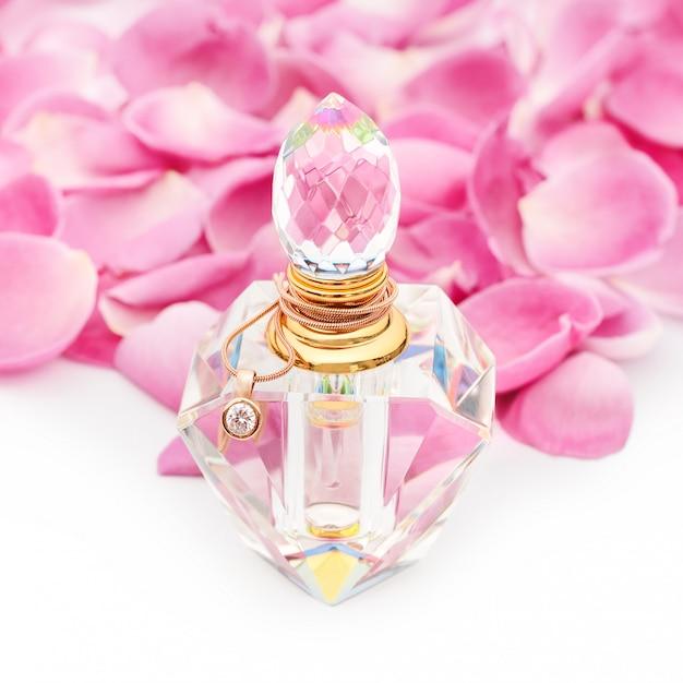 Bottiglia di profumo con collana tra petali di fiori. profumeria, cosmetici, collezione di fragranze Foto Premium