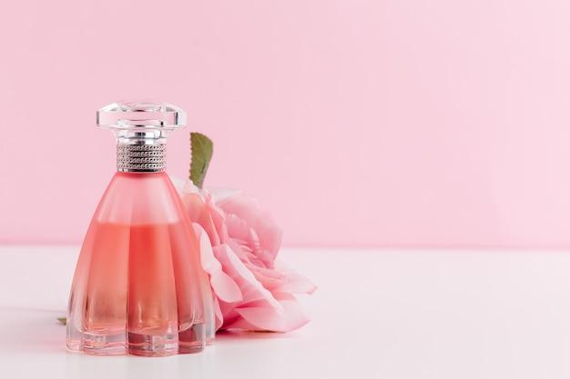 Bottiglia di profumo con fiori su colore Foto Premium