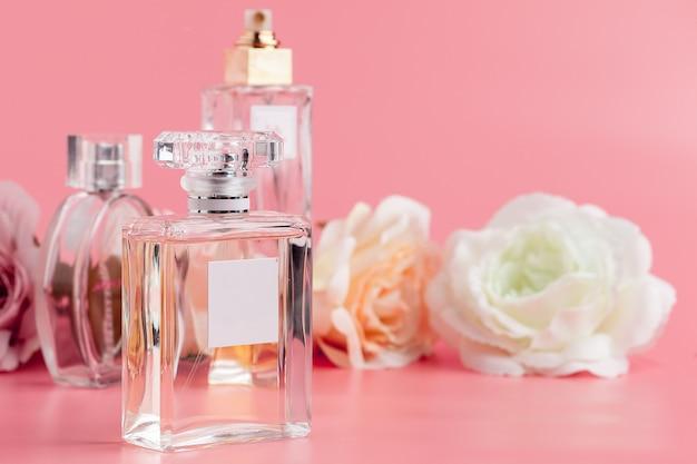Bottiglia di profumo con rose su tessuto rosa Foto Premium