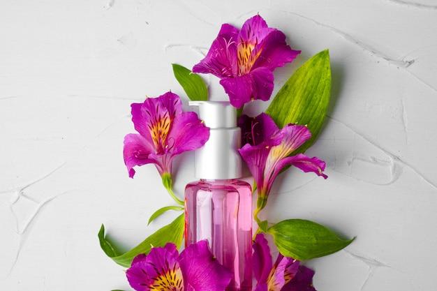 Bottiglia di profumo in un mazzo di fiori freschi Foto Premium