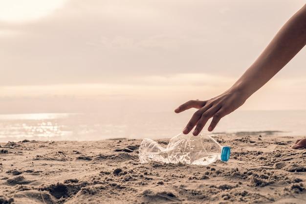 Bottiglia di raccolta a mano in plastica sulla spiaggia, volontaria per salvare l'ambiente Foto Premium