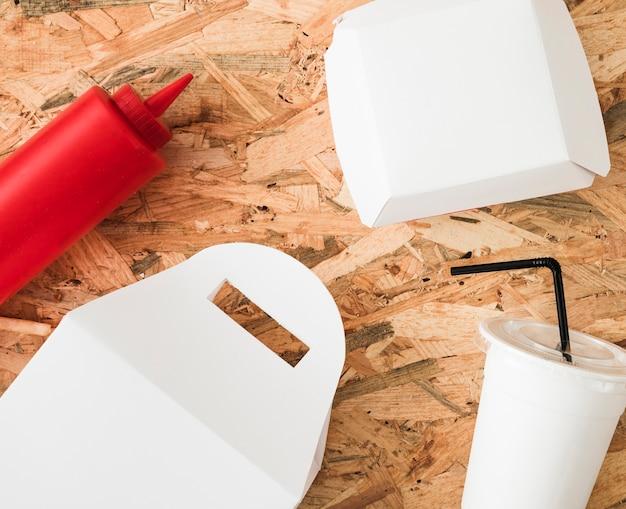 Bottiglia di salsa; pacchetto bianco e bevanda usa e getta sul fondale in legno Foto Gratuite