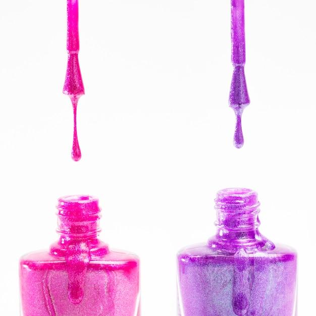 Bottiglia di smalto rosa e viola su sfondo bianco Foto Gratuite