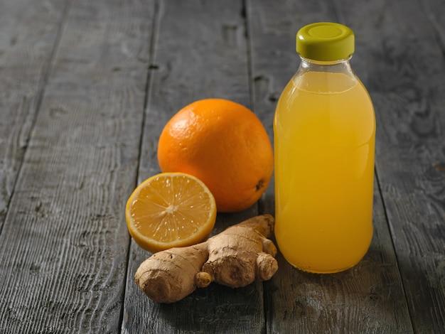 Bottiglia di vetro con una bevanda di radice di zenzero, limone, arancia, miele e cannella su un tavolo di legno nero. Foto Premium