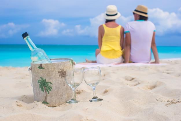 Bottiglia di vino bianco e due bicchieri di sfondo felice coppia sulla spiaggia di sabbia Foto Premium