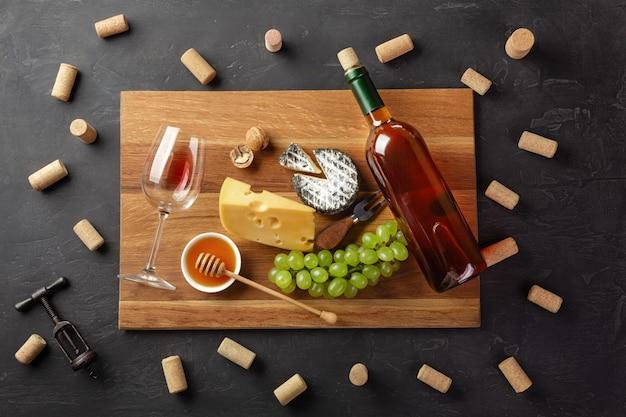 Bottiglia di vino bianco, testa di formaggio, grappolo d'uva, miele, noci e bicchiere di vino sul tagliere con tappi di sughero e cavatappi Foto Premium