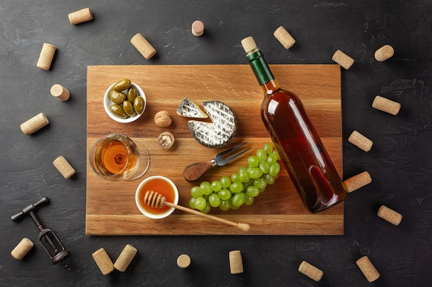 Bottiglia di vino bianco, testa di formaggio, grappolo d'uva, miele, noci e bicchiere di vino Foto Premium