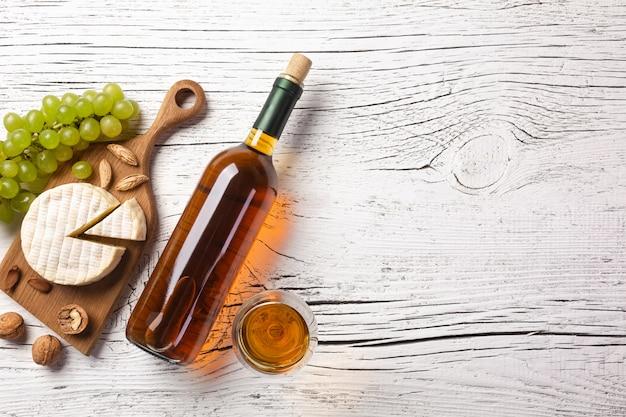 Bottiglia di vino bianco, uva, formaggio e bicchiere di vino sul bordo di legno bianco Foto Premium