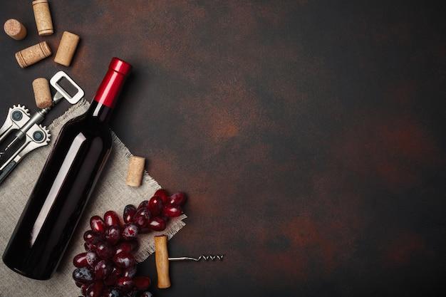 Bottiglia di vino, cavaturaccioli e tappi di sughero, sulla vista superiore del fondo arrugginito Foto Premium