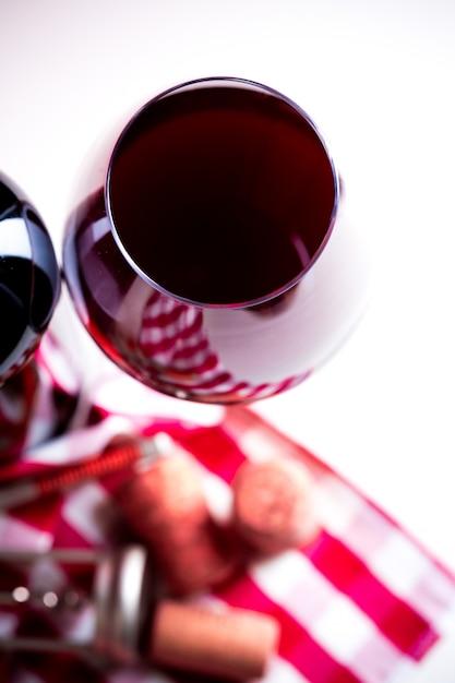 Bottiglia di vino con il vetro di vino su fondo di legno bianco Foto Premium