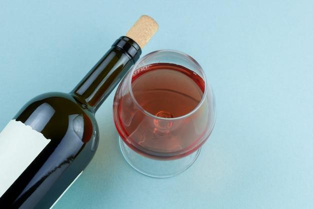 Bottiglia di vino e bicchiere di vino con vista dall'alto del vino rosso su sfondo blu Foto Premium